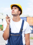 Lavoratore di porto con il dispositivo della radio del walkie sul lavoro Fotografia Stock Libera da Diritti