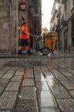 Lavoratore di pulizia della via con il pavimento bagnato fotografia stock libera da diritti