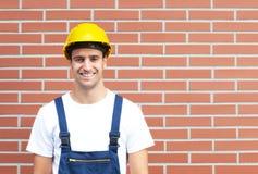 Lavoratore di risata davanti ad un muro di mattoni Immagine Stock