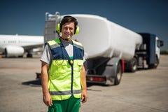 Lavoratore di risata dell'aeroporto con il camion su fondo vago fotografia stock