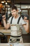 Lavoratore di servizio professionale con il trapano elettrico ed il cacciavite in mani immagini stock libere da diritti