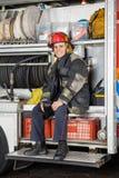 Lavoratore felice che si siede nei vigili del fuoco fotografia stock libera da diritti