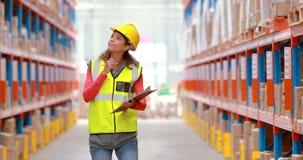Lavoratore femminile del magazzino che controlla azione per vedere se c'è spedire stock footage