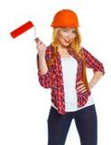Lavoratore femminile divertente di contruction in un casco con il rullo a disposizione Immagine Stock