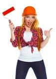 Lavoratore femminile divertente di contruction in un casco con il rullo a disposizione Fotografie Stock
