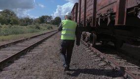 Lavoratore ferroviario con il walkie-talkie vicino ai vagoni video d archivio
