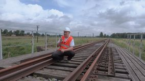 Lavoratore ferroviario sul walkie-talkie sul ponte ferroviario stock footage