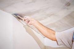 Lavoratore manuale con la parete che intonaca gli strumenti fotografia stock libera da diritti