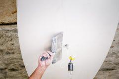 Lavoratore manuale con la parete che intonaca gli strumenti immagini stock