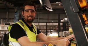Lavoratore maschio che guida carrello elevatore nell'industria di bottiglia video d archivio
