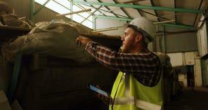 Lavoratore maschio che per mezzo della compressa digitale 4k archivi video