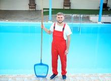 Lavoratore maschio che pulisce stagno all'aperto immagine stock libera da diritti