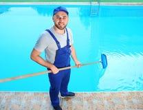 Lavoratore maschio che pulisce stagno all'aperto con la rete immagine stock libera da diritti