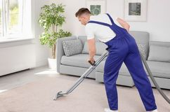 Lavoratore maschio che rimuove sporcizia dal tappeto immagine stock