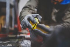Lavoratore maschio che ripara pietra, bordo che affila nell'officina di servizio dello sci, piano di scorrimento degli sci affila fotografia stock libera da diritti