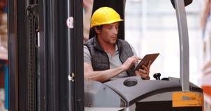Lavoratore maschio del magazzino che per mezzo della compressa digitale stock footage
