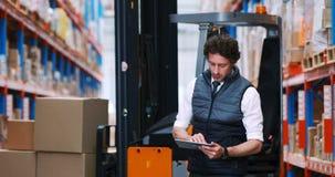 Lavoratore maschio del magazzino che per mezzo della compressa digitale archivi video