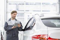 Lavoratore maschio di riparazione che utilizza il PC della compressa mentre facendo una pausa automobile nell'officina Fotografia Stock