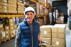 Lavoratore maschio senior del magazzino o un supervisore che tira un camion di pallet con le scatole Immagini Stock