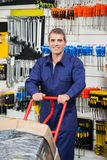 Lavoratore maturo che spinge carrello nel negozio dell'hardware Fotografia Stock Libera da Diritti