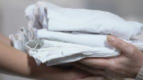 Lavoratore medico che dà le lenzuola pulite pazienti anziane nella casa di cura, carità archivi video