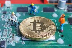 Lavoratore miniatura che scava e che estrae Bitcoin su circ stampato immagini stock