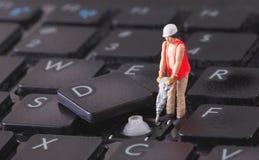 Lavoratore miniatura con il trapano che lavora alla tastiera Immagine Stock