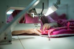 Lavoratore nel cucito di industria tessile immagine stock