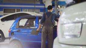Lavoratore nel servizio automatico che prepara automobile per il sistema diagnostico professionale, fine su Immagini Stock Libere da Diritti