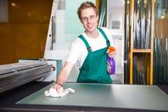 Lavoratore nell'officina del vetraio che pulisce un vetro immagini stock libere da diritti