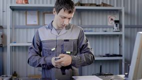Lavoratore professionista che per mezzo del dispositivo speciale per le parti di metallo dell'interno video d archivio