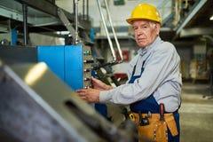 Lavoratore senior che aziona le unità a macchina alla fabbrica immagini stock libere da diritti