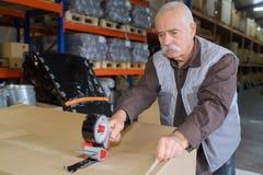 Lavoratore senior che lega scatola con un nastro in magazzino immagini stock