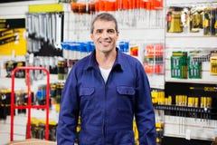 Lavoratore sicuro che sorride nel negozio dell'hardware Fotografia Stock Libera da Diritti