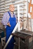 Lavoratore soddisfatto alla fabbrica delle finestre del PVC immagini stock libere da diritti