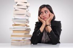 Lavoratore sollecitato che esamina un mucchio dei libri Immagini Stock