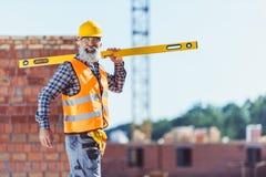 Lavoratore sorridente in maglia ed elmetto protettivo riflettenti che cammina con il livello di spirito attraverso fotografie stock