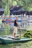 Lavoratore su una barca nel lago Houhai, Pechino, Cina Immagine Stock