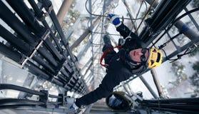 Lavoratore sulla torre di comunicazione Fotografia Stock