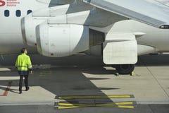 Lavoratore a terra che controlla l'aereo Fotografie Stock