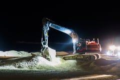 Lavoratore a terra che lavora alla notte nello scuro con una macchina scavatrice che muove la sabbia alla spiaggia per manutenzio fotografia stock libera da diritti