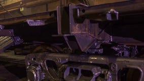 Lavoratore in una fabbrica per la fabbricazione di treni il lavoratore sulla fabbrica controlla i carrelli del treno Operaio Immagini Stock