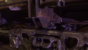 Lavoratore in una fabbrica per la fabbricazione di treni il lavoratore sulla fabbrica controlla i carrelli del treno Operaio Fotografia Stock Libera da Diritti