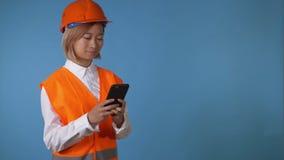 Lavoratore in uniforme che manda un sms sullo smartphone video d archivio