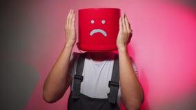 Lavoratore in uniforme con il secchio rosso sulla sua testa triste video d archivio