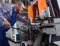 Lavoratore vicino alla fresatrice alla fabbrica fotografie stock libere da diritti