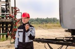 Lavoratore vicino a pumpjack, alla testa di pozzo ed al semirimorchio cisterna nel giacimento di petrolio Fotografie Stock
