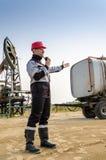 Lavoratore vicino a pumpjack e semirimorchio cisterna nel giacimento di petrolio Immagine Stock