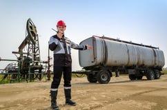 Lavoratore vicino a pumpjack e semirimorchio cisterna nel giacimento di petrolio Fotografie Stock Libere da Diritti