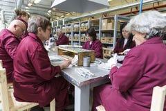 Lavoratori ad una catena di montaggio nella fabbrica della munizione Immagini Stock